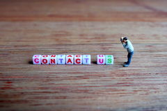 Μικροσκοπικός φωτογράφος, που παίρνει την εικόνα της επαφής εμείς κύβοι Στοκ εικόνες με δικαίωμα ελεύθερης χρήσης