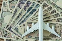 Μικροσκοπικό άσπρο αεροπλάνο στο σωρό των ιαπωνικών τραπεζογραμματίων γεν ως FI Στοκ Εικόνες