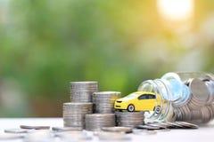 Μικροσκοπικό κίτρινο πρότυπο αυτοκινήτων στο σωρό των χρημάτων νομισμάτων στο μπουκάλι γυαλιού στο πράσινο υπόβαθρο φύσης, που κε στοκ φωτογραφία