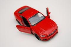Μικροσκοπικό κόκκινο αυτοκίνητο παιχνιδιών Στοκ Φωτογραφία