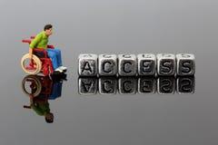 Μικροσκοπικό πρότυπο άτομο κλίμακας σε μια αναπηρική καρέκλα με την πρόσβαση λέξης στις χάντρες Στοκ εικόνες με δικαίωμα ελεύθερης χρήσης