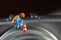 Μικροσκοπικό πρότυπο αριθμού συντήρησης που τίθεται στο μέρος φακών της ψηφιακής κάμερα Στοκ Εικόνα
