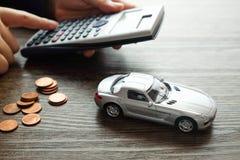 Μικροσκοπικό πρότυπο αυτοκινήτων και ένας σωρός του νομίσματος στο ξύλινο υπόβαθρο, Calc Στοκ φωτογραφία με δικαίωμα ελεύθερης χρήσης