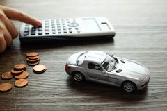 Μικροσκοπικό πρότυπο αυτοκινήτων και ένας σωρός του νομίσματος στο ξύλινο υπόβαθρο, Calc Στοκ Φωτογραφία