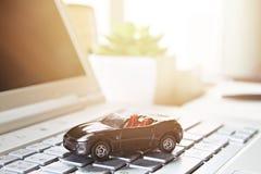 Μικροσκοπικό πρότυπο αυτοκινήτων στο lap-top υπολογιστών Στοκ Φωτογραφία