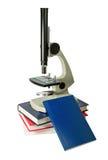 Μικροσκόπιο και βιβλία που απομονώνονται στο λευκό Στοκ Εικόνα
