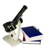 Μικροσκόπιο και βιβλία που απομονώνονται στο λευκό Στοκ Φωτογραφίες
