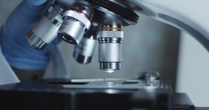 Μικροσκόπιο με το φακό μετάλλων στο εργαστήριο απόθεμα βίντεο