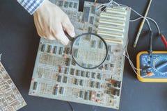 Μικροϋπολογιστής ή νανο ηλεκτρονική έννοια πινάκων reapir, ενίσχυση λαβής χεριών - γυαλί φ στοκ εικόνες