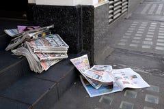 Μικρού σχήματος εφημερίδες που εγκαταλείπονται σε μια πόρτα καταστημάτων Στοκ Εικόνες