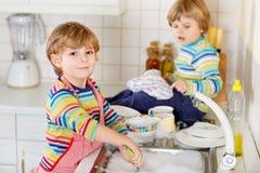 Μικρός αστείος αρωγός δύο στην κουζίνα με τα πιάτα πλύσης Στοκ εικόνα με δικαίωμα ελεύθερης χρήσης