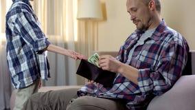 Μικρός γιος που ρωτά τον πατέρα του για τα χρήματα για τη μετάβαση στον καφέ με το φίλο, χρηματοδότηση στοκ φωτογραφία με δικαίωμα ελεύθερης χρήσης