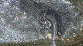 Μικρός εκσακαφέας στην απόρριψη στερεών αποβλήτων, ρύπανση από τα από φιλμ μικρού μήκους