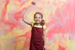 Μικρός ευτυχής αρχιμάγειρας κοριτσιών στο μαγειρεύοντας εργαλείο εκμετάλλευσης ποδιών μαγείρων Στοκ Φωτογραφίες