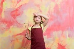 Μικρός κουρασμένος αρχιμάγειρας κοριτσιών στο μαγειρεύοντας εργαλείο εκμετάλλευσης ποδιών μαγείρων Στοκ Εικόνα