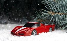 Μικρός, κόκκινος, αυτοκίνητο παιχνιδιών στο χιόνι κοντά fir-tree Στοκ φωτογραφία με δικαίωμα ελεύθερης χρήσης