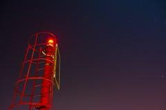 Μικρός κόκκινος φάρος κάτω από έναν έναστρο ουρανό Στοκ φωτογραφία με δικαίωμα ελεύθερης χρήσης