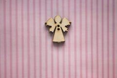 Μικρός ξύλινος αριθμός αγγέλου για το ρόδινο ριγωτό υπόβαθρο Σχέδιο ευχετήριων καρτών Δώρο και παρούσα έννοια Ανασκόπηση γενεθλίω Στοκ Φωτογραφίες