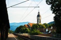 Μικρός σιδηροδρομικός σταθμός, ένας πύργος με το ρολόι, σπίτια με τις στέγες κεραμιδιών και βουνά στο υπόβαθρο, Nagymaros στοκ εικόνα με δικαίωμα ελεύθερης χρήσης