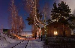 Μικρός σιδηροδρομικός σταθμός τοπίων πόλεων που καλύπτουν με το χιόνι, πυροβολισμός νύχτας Στοκ Εικόνες