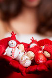 Μικρός χιονάνθρωπος με το κόκκινο μαντίλι και καπέλο στα χέρια ενός προτύπου CH Στοκ Φωτογραφίες