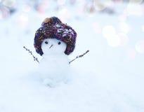 Μικρός χιονάνθρωπος σε μια πλεκτή ΚΑΠ στο χιόνι το χειμώνα Εορταστικό υπόβαθρο με έναν καλό χιονάνθρωπο Στοκ εικόνα με δικαίωμα ελεύθερης χρήσης