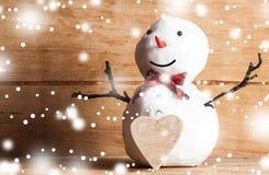 Μικρός χιονάνθρωπος στο ξύλινο γραφείο Στοκ Εικόνα