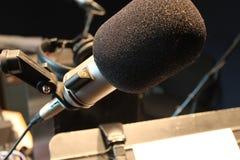 Μικρόφωνο, ακουστικά και στάση μουσικής στο στούντιο καταγραφής Στοκ Φωτογραφία