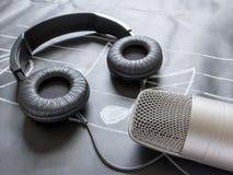 Μικρόφωνο και ακουστικά στη μαύρη σημείωση μουσικής Στοκ φωτογραφίες με δικαίωμα ελεύθερης χρήσης