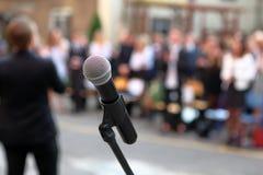 Μικρόφωνο και στάση μπροστά από graduation ceremony audience ag στοκ φωτογραφία