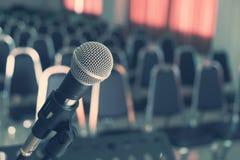Μικρόφωνο πέρα από τις θολωμένες έδρες στη αίθουσα συνδιαλέξεων Στοκ Εικόνες
