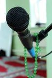 Μικρόφωνο σε ένα πράσινα υπόβαθρο και rosary Στοκ φωτογραφία με δικαίωμα ελεύθερης χρήσης