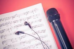Μικρόφωνο στα φύλλα μουσικής Η έννοια της δημιουργίας της μουσικής Στοκ Εικόνα