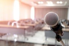 Μικρόφωνο στην περίληψη που θολώνεται της ομιλίας στο δωμάτιο σεμιναρίου στοκ φωτογραφία