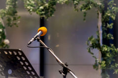 Μικρόφωνο στη αίθουσα συναυλιών ή τη αίθουσα συνδιαλέξεων μαλακή και το ύφος θαμπάδων για το υπόβαθρο Μικρόφωνο πέρα από την αφηρ Στοκ φωτογραφία με δικαίωμα ελεύθερης χρήσης