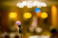 Μικρόφωνο στη αίθουσα συναυλιών ή τη αίθουσα συνδιαλέξεων μαλακή και το ύφος θαμπάδων για το υπόβαθρο Μικρόφωνο πέρα από την αφηρ Στοκ Φωτογραφίες