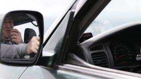 Μικρόφωνο χεριών εκμετάλλευσης ατόμων και ομιλία στο ραδιόφωνο στο αυτοκίνητό του απόθεμα βίντεο