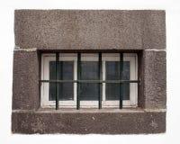 Μικρό άσπρο ξύλινο παράθυρο με τα πλακάκια γυαλιού που καλύπτονται από τους φραγμούς χάλυβα σε ένα μεγάλο γκρίζο πλαίσιο πετρών σ στοκ εικόνες με δικαίωμα ελεύθερης χρήσης