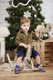 Μικρό αγοριών άλογο λικνίσματος γύρου ξύλινο μπροστά από το χριστουγεννιάτικο δέντρο Στοκ Εικόνα