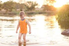 Μικρό αγοριών σε μια λίμνη στην ανατολή Στοκ εικόνες με δικαίωμα ελεύθερης χρήσης