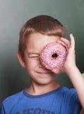 Μικρό αγόρι με doughnut Στοκ φωτογραφία με δικαίωμα ελεύθερης χρήσης