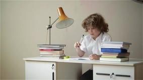 Μικρό αγόρι που μελετά ή που κάνει την εγχώρια εργασία, το μαθητή που μελετούν με το σημειωματάριο και τα βιβλία στον πίνακα φιλμ μικρού μήκους