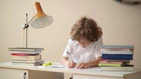 Μικρό αγόρι που μελετά ή που κάνει την εγχώρια εργασία, το μαθητή που μελετούν με το σημειωματάριο και τα βιβλία στον πίνακα απόθεμα βίντεο