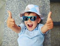 Μικρό αγόρι στα γυαλιά ηλίου που δίνουν τους αντίχειρες επάνω στην οδό s Στοκ φωτογραφία με δικαίωμα ελεύθερης χρήσης