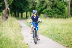 Μικρό αγόρι στο οδηγώντας ποδήλατο κρανών στο πάρκο Στοκ Εικόνες
