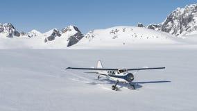 Μικρό αεροπλάνο που προσγειώνεται στο χιόνι στα από την Αλάσκα βουνά Στοκ φωτογραφία με δικαίωμα ελεύθερης χρήσης