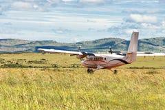 Μικρό αεροπλάνο προωστήρων επιβατών που προσγειώνεται στο πράσινο λιβάδι Στοκ Εικόνες