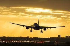 Μικρό αεροπλάνο που προσγειώνεται κατά τη διάρκεια της ανατολής Στοκ Εικόνα