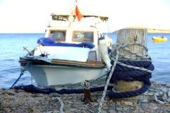 Μικρό αλιευτικό σκάφος που δένεται στον ξύλινο πόλο Στοκ Εικόνες