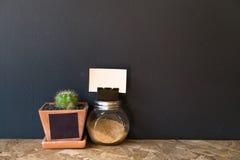 Μικρό βάζο κάκτων με ένα μικροσκοπικό καφετί μπουκάλι ζάχαρης Στοκ εικόνα με δικαίωμα ελεύθερης χρήσης